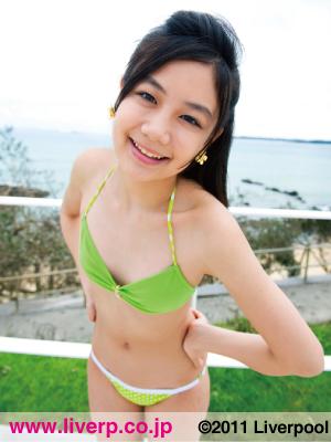 淡い黄緑の水着を着て腰に手を当てて笑顔を見せる清水富美加